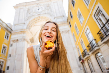 Young woman holding portuguese egg tart pastry called pastel de Nata outdoors on the triumphal arch background in Lisbon