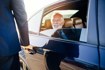 Senior business man sitting in his limousine. Business concept. Back light.