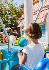 Child controls the machine. Rides on attractions.Gardaland Theme Amusement Park in Castelnuovo Del Garda, Verona, Italy.