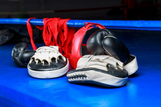 Boxing gloves and elastic bandage lying on the floor of the ring after a workout