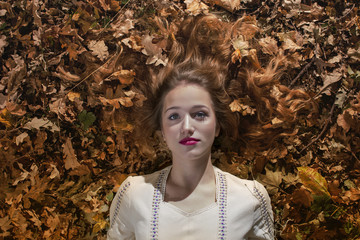Young woman laying on a bed of dry leafs