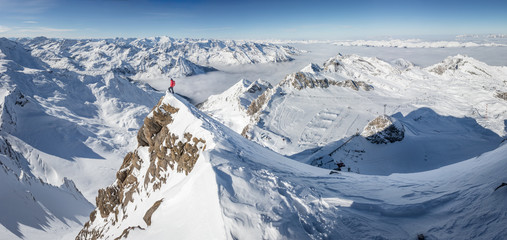 Mountaineer standing on a snow capped mountain summit