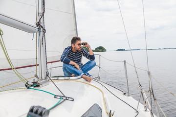 man sits on sailing yacht and looks through binoculars