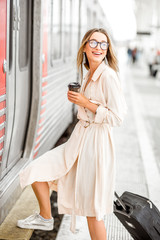 Young and beautiful woman with coffee cup and luggage boarding in the train at the railway station