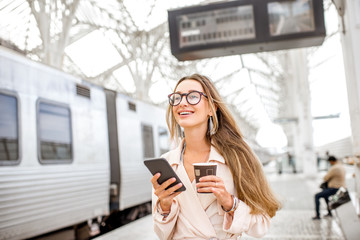 Portrait of a young woman using smart phone at the railway station with information board on the background
