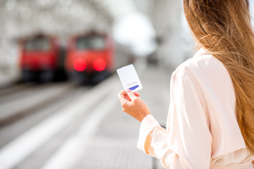 Holding a ticket with empty space with trains on the background at the railway station