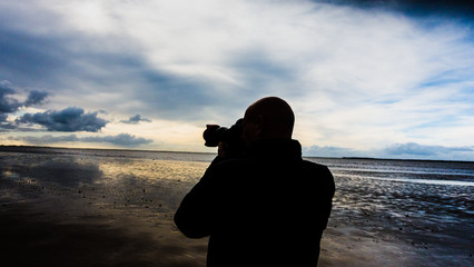 anonymous Passionate photographer shoots the landscape in moody silhouette.