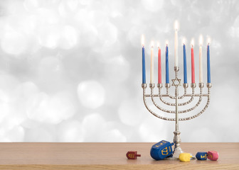 Hanukkah Jewish holiday background with menorah (Judaism candelabra)  burning candles and traditional Dreidrel game toy on wood table and on white silver winter snow bokeh