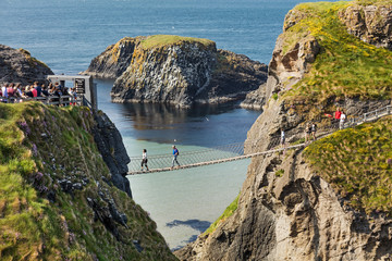 Fotobehang Eiland Thousands of tourists visiting Carrick-a-Rede Rope Bridge in County Antrim of Northern Ireland, hanging 30m above rocks and spanning 20m, linking mainland with the tiny island of Carrickarede