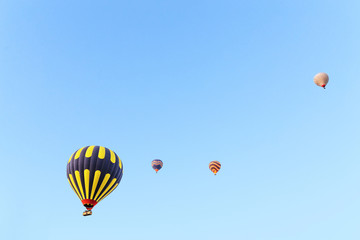 Many unrecognizable colorful hot air balloons against blue sky