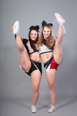 Two Cheerleaders Performing A Stretch