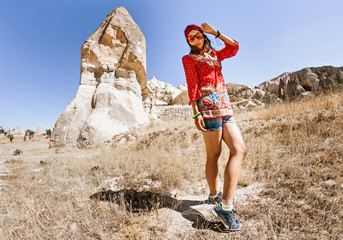 A happy young tourist eastern asian girl in traditional clothes travels among cappadocia landscape and cave towns at summer