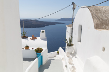 A balcony with plants in jugs and a view on a sea, mountains and city with white houses