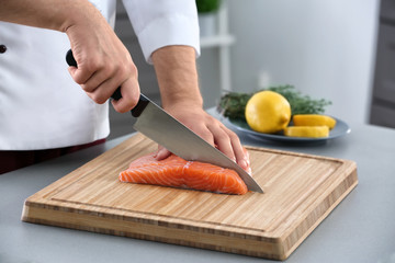 Chef cutting fresh salmon fillet in kitchen