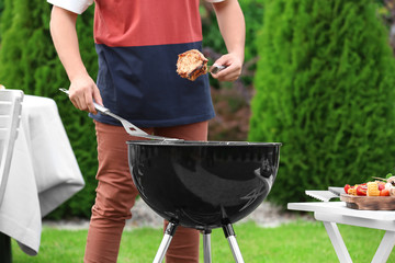 Man cooking tasty steaks on barbecue grill, outdoors