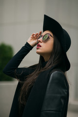 Closeup shot of elegant brunette lady dressed in black coat, stylish hat and glasses, looking up