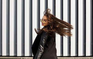Lifestyle portrait of pretty young model in sunglasses with hair blowing in wind walking at the street