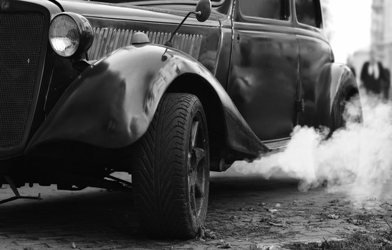 The retro car smokes in the city streets. Black and white image