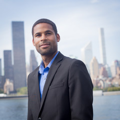 Portrait of young bright African American professional with NYC Skyline, looking sharp and confident
