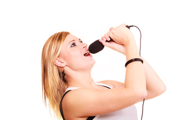 Blonde woman singing to microphone, profile view
