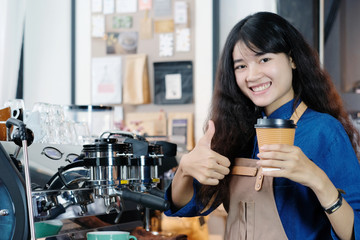 Young asian woman barista holding take away coffee cup paper and thumb up with smiling face at cafe counter background, small business owner, food and drink industry concept