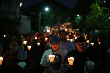 Catholic faithfuls participate in a procession commemorating the 28th anniversary of the murder of six Jesuit priests and two employees in San Salvador
