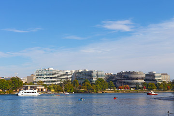 Washingtonians enjoy water activities on a warm day in autumn. Potomac River waterfront buildings and boats on the river waters.