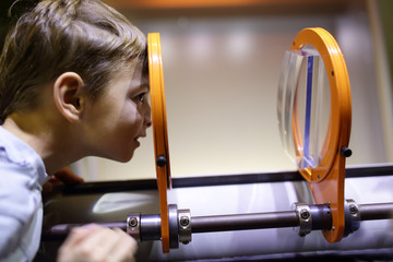Child looking through magnifying glass system