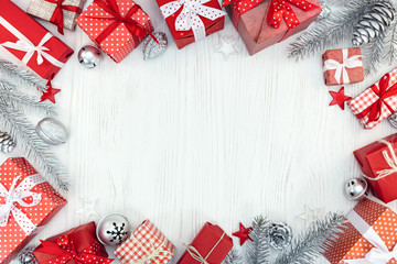 christmas gift boxes, decorations and silver fir tree branches on white wooden table background with copy space