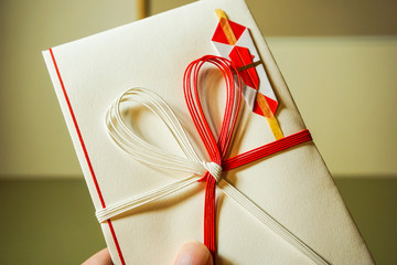 お祝い金、ご祝儀、結婚祝い、出産祝い用の袋を手に持つ