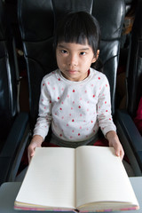 Kid reading book in a flight