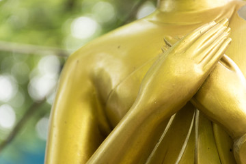 Closeup hands of buddha statue touching the heart on chest