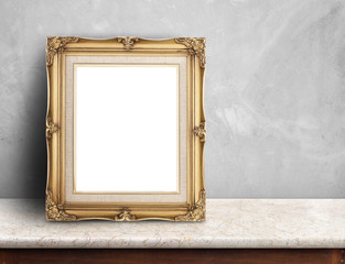 Blank Gold victorian picture frame on white marble table at grey concrete wall,Template mock up for adding your design and leave space beside frame for adding more text.