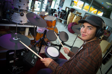 Young blond caucasian boy plays drums in shop
