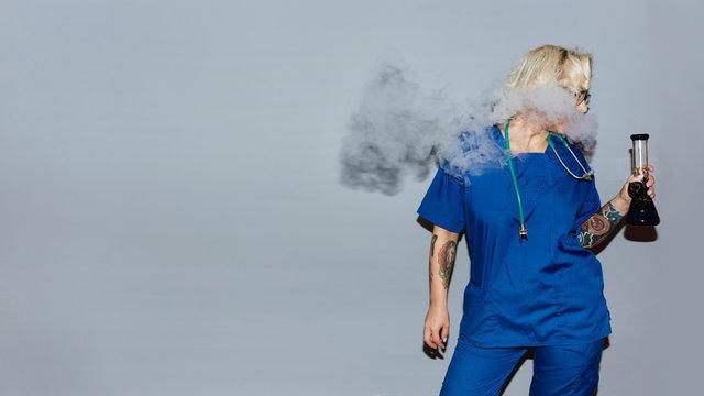 Nurse in blue uniform smoking bong against gray wall