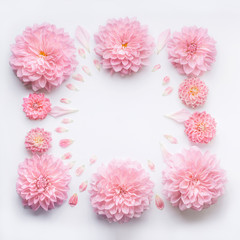 Frame of pink pale flowers with petals on white desktop background, flat lay, top view. Creative floral layout or mock up for greeting card for Mothers day, wedding , happy event or birthday