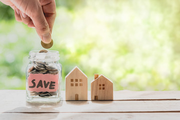 Hand putting coin in glass jar of coin for saving money for buying house. Real estate concept