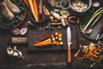Colorful sliced carrots with knife on wooden cutting board on rustic kitchen table background with root vegetables ingredients for tasty vegetarian cooking, top view. Healthy and clean seasonal food