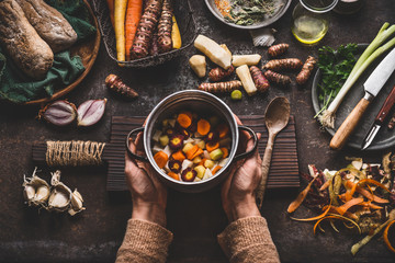 Female woman hands holding pan with diced colorful vegetables on dark rustic kitchen table with vegetarian cooking ingredients and tools. Healthy and clean seasonal food cooking and eating concept