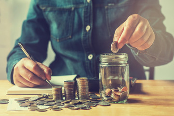 businesswoman saving money with putting coins in glass, finance accounting concept