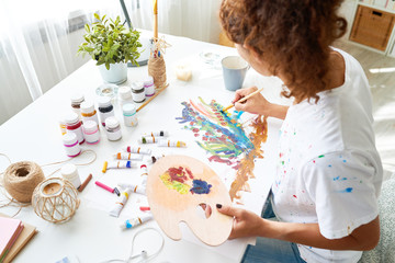 High angle portrait of inspired young woman painting beautiful oil picture sitting at desk in small art studio