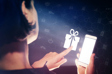 Image of a girl with a smartphone in hands. She presses on the gift icon. Concept of gift giving, choice of gifts.