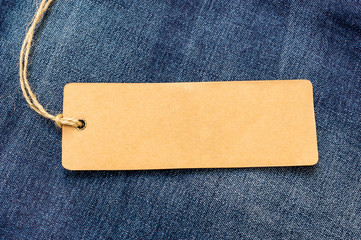 Blank paper label on a blue jeans texture.