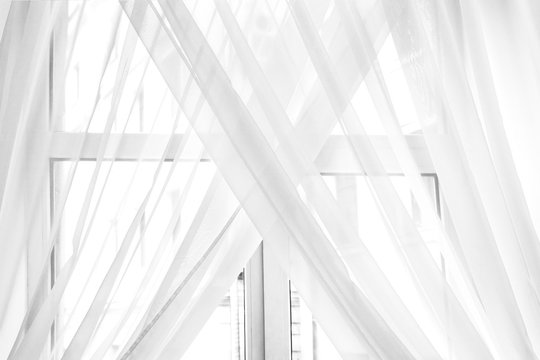 White sheer curtain texture background in daylight atmosphere of apartment's interior. Black and white transparent curtain background.Curtain made of a light fabric that filters the light