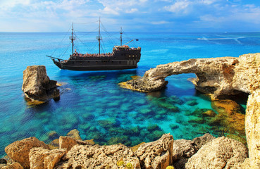 Poster Cyprus The bridge of love or love bridge. Pirate ship sailing near famous Bridge of Love near Ayia Napa, Cyprus.