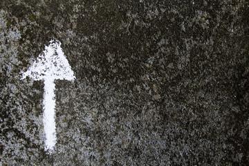 chalk drawing on asphalt: white arrow sign