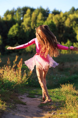 Beautiful teen girl  Is dancing outside at  summer sunset
