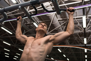 Low angle portrait of muscular young man with bare chest working out using machines  in modern gym against background on metal ceiling