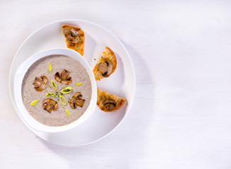 Soup with champignons, leek and crispy croutons on white background, top view.