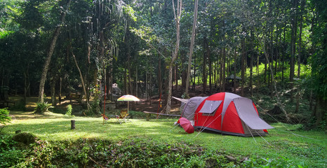 nature landscape red camping tent with colorful umbrella under tree on green grass meadow and waterfall in jungle for picnic on holiday relax travel and winter season with sunlight at PhaTat waterfall